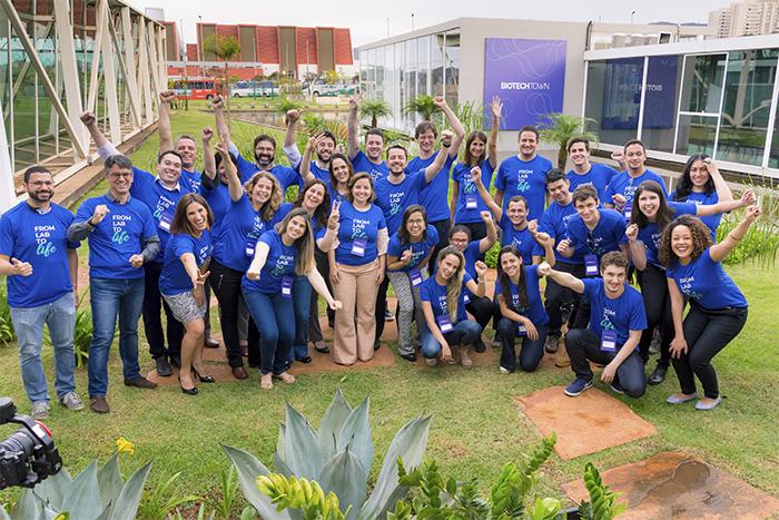 """Na foto aparecem cerca de 30 pessoas em um jardim, que fazem parte da primeira turma de startups investidas pelo BiotechTown. Todos estão com as mãos pra cima, como se estivessem comemorando, e estão vestidas com a camisa do BiotechTown. Nas camisas está escrito """"fom lab to life""""."""