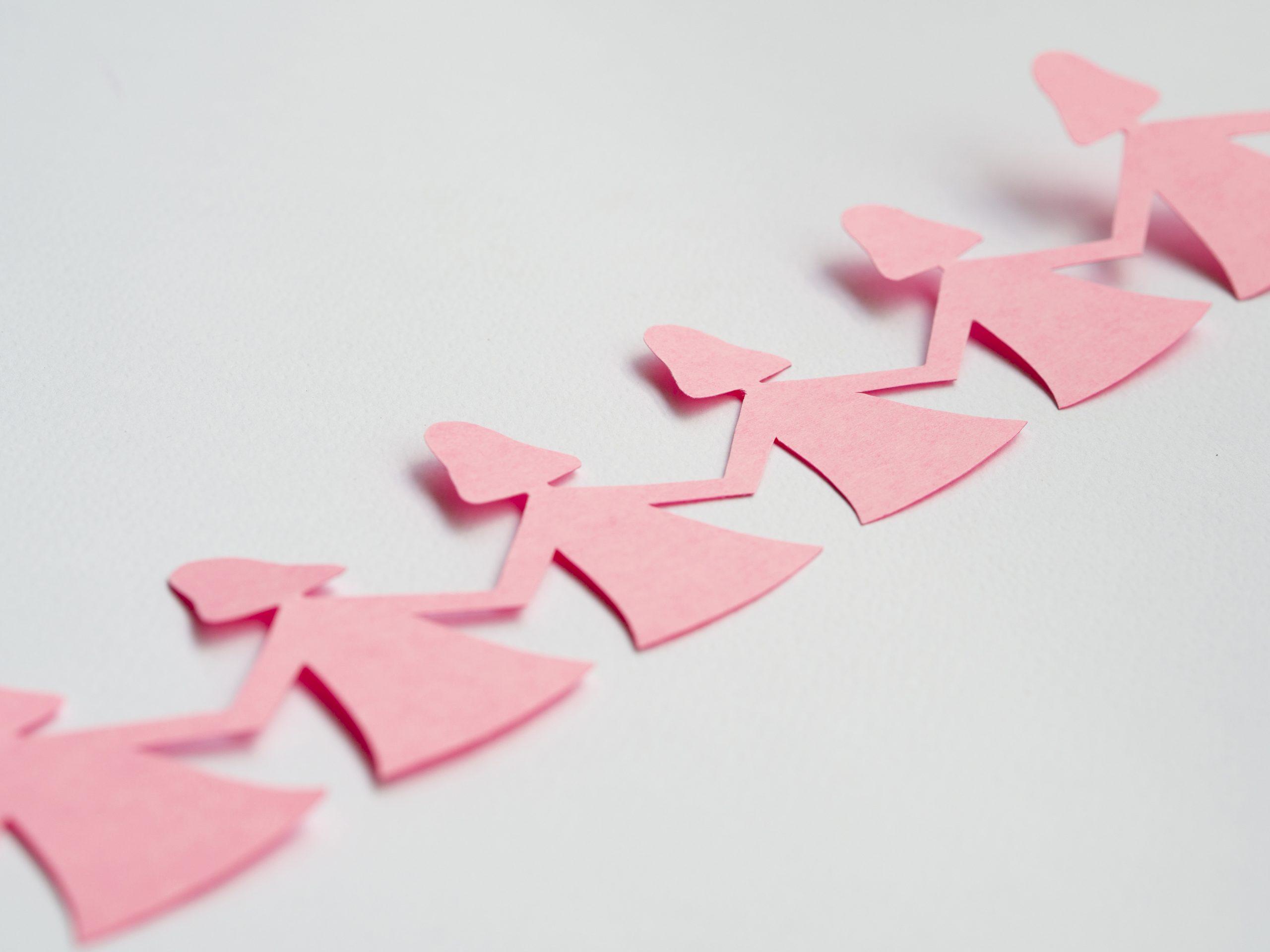 Recorte em um papel rosa representando várias mulheres de mãos dadas