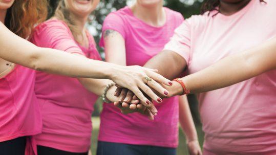Na foto cinco mulheres estão juntando suas mãos no centro da foto. Todas as mulheres estão vestidas de rosa